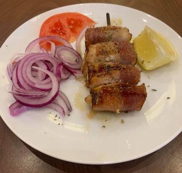 Une pièce de Souvlaki (brochette) de poulet au bacon.